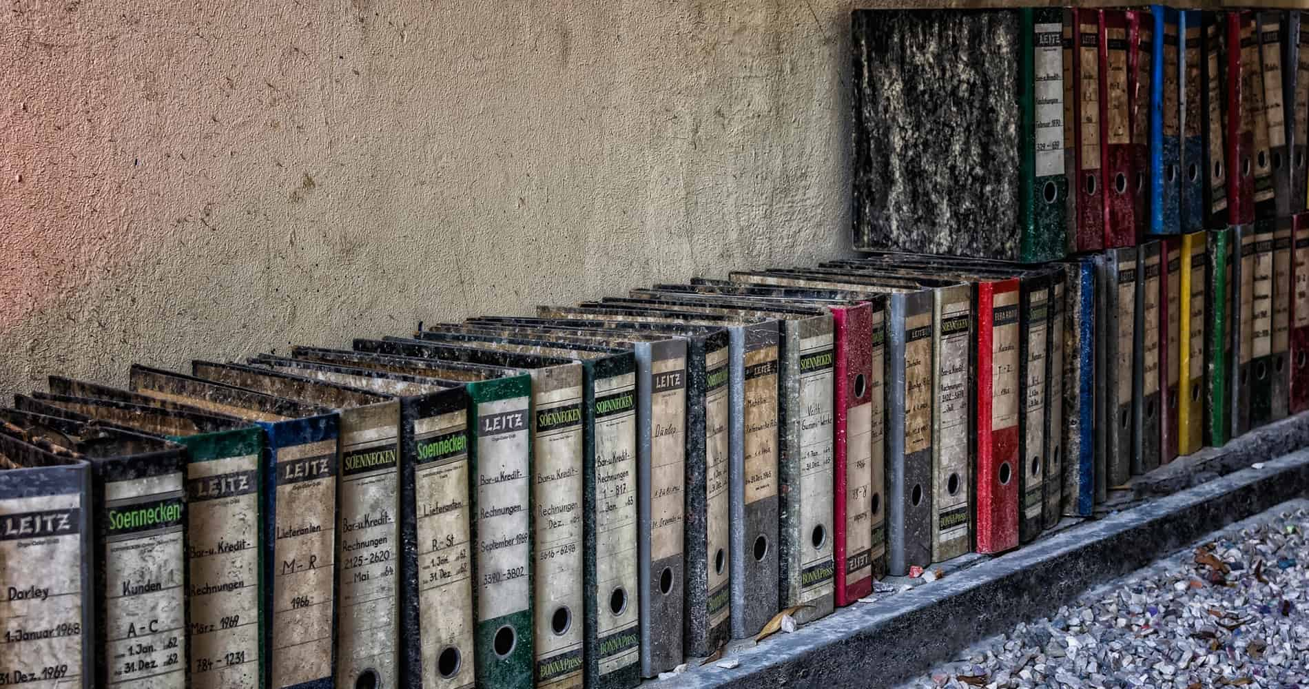 A line of old index binders lined up along a wall.